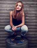 Happy beautiful woman in blue jeans sitting on the iron barrel o Stock Image