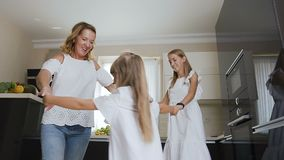 Happy beautiful woman with children having fun on kitchen are dancing in circle and holding hands. Healthy mother and stock video