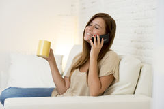 Happy beautiful woman on couch talking on mobile phone relaxed and cheerful smiling at home sofa Stock Photos