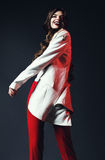 Happy beautiful woman dancing in white coat in red pants Royalty Free Stock Photography