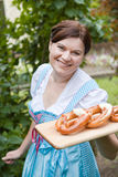 Happy beautiful woman in dirndl dress holding Oktoberfest pretz. Happy beautiful girl in dirndl dress holding Oktoberfest pretzel in hands stock photos