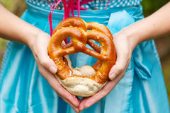 Happy beautiful woman in dirndl dress holding Oktoberfest pretz. Oktoberfest pretzels in hands of a woman in traditional German clothes, blue bavarian dirndl royalty free stock images