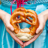 Happy beautiful woman in dirndl dress holding Oktoberfest pretz. Oktoberfest pretzels in hands of a woman in traditional German clothes, blue bavarian dirndl royalty free stock photography