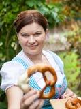 Happy beautiful woman in dirndl dress holding pretzel Stock Image