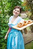Happy beautiful woman in dirndl dress holding pretzel Royalty Free Stock Image
