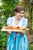 Happy beautiful woman in dirndl dress holding pretzel Royalty Free Stock Photos