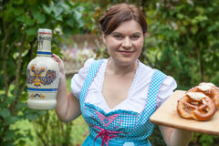 Happy beautiful woman in dirndl dress holding pretzel Royalty Free Stock Images