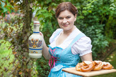 Happy beautiful woman in dirndl dress holding pretzel Stock Photos