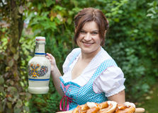 Happy beautiful woman in dirndl dress holding pretzel Stock Images
