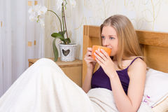 Happy beautiful woman drinking coffee or tea in bedroom Royalty Free Stock Images