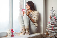 Happy beautiful woman drinking hot coffee sitting on window sill Stock Image