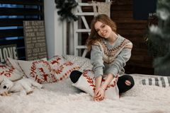 Happy beautiful woman in fashionable knitted sweater hugs. A pillow sitting on the bed royalty free stock photo