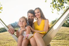 Happy beautiful woman and handsome husband posing together with their daughter. Happy beautiful women and her handsome husband posing together with their cute Royalty Free Stock Photo