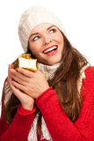 Happy beautiful woman holding Christmas present. A beautiful happy young woman holding a small Christmas gift. Isolated on white Royalty Free Stock Photography