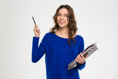 Happy beautiful woman holding folders and pointing away with pen Royalty Free Stock Image