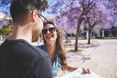 Happy beautiful woman holding map laughing to her boyfriend. Portrait of happy beautiful women holding map laughing to her boyfriend Royalty Free Stock Images