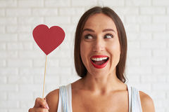 Happy beautiful woman holding red paper heart and look it. White brick wall on background Stock Image