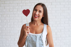 Happy beautiful woman holding red paper heart near of her face Stock Images