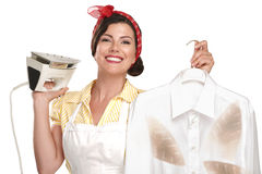 Happy beautiful woman housewife ironing a shirt Stock Photos