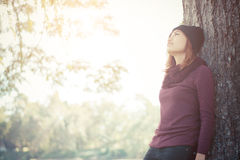 Happy beautiful woman leaning against a tree looking on the sky Royalty Free Stock Image