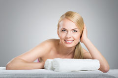 Happy beautiful woman leaning on table with towels. Front portrait of happy beautiful woman leaning on table with towels Royalty Free Stock Photos