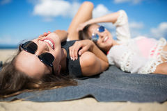Happy beautiful woman lying on blanket on beach with friend Royalty Free Stock Photo