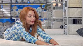 Happy beautiful woman lying on a new orthopedic mattress at furnishings store. Cheerful female customer trying comfortable beds, looking away smiling, copy stock video