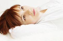 Happy beautiful woman lying on white fur plaid Royalty Free Stock Photos