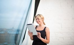 Smiling hipster girl watching video in social network via touch pad, standing in modern interior. stock photos