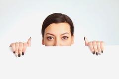 Happy beautiful Woman peeking behind a whiteboard royalty free stock image