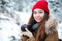 Happy beautiful woman photograher taking photos in winter forest. Portrait of happy beautiful young woman photograher holding camera and taking photos in winter stock images