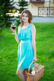 Happy beautiful woman with picnic basket drinking wine in park Royalty Free Stock Photo