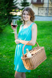 Happy beautiful woman with picnic basket and glass of wine in pa Royalty Free Stock Photos