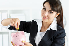 Happy beautiful woman putting pin money coins into pink piggyban Stock Images