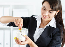 Happy beautiful woman putting pin money coins into white piggyba Stock Images