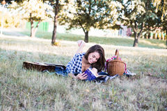 Happy and beautiful woman reading book in nature royalty free stock image