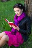 Happy beautiful woman reading book in summer park Royalty Free Stock Photography