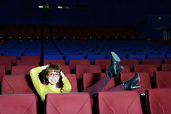 Happy beautiful woman in red glasses lifted her legs on chair. In movie theater royalty free stock images