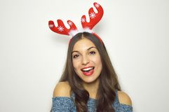 Happy beautiful woman with reindeer horns on her head looks at camera on white background. Christmas holidays. Happy beautiful woman with reindeer horns on her Stock Photo