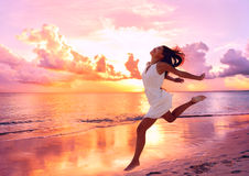 Happy beautiful woman running at beach sunset. Happy beautiful free woman running on the beach at sunset jumping playful having fun in serene picturesque sunset Royalty Free Stock Images