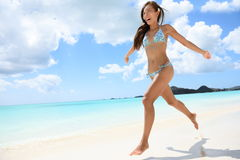 Happy beautiful woman running on the beach. On travel vacation beach holidays in the Caribbean. Image full of aspiration and joy with multicultural Caucasian / Stock Image