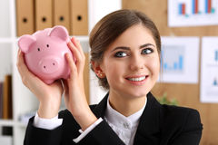 Happy beautiful woman shake funny piggybank. And listen sound of inside detecting amount. Future needs loan, education or mortgage credit, spend vacation of Stock Image