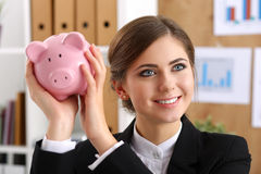 Happy beautiful woman shaking funny piggybank. And listening sound of inside detecting amount. Budgeting expenses concept. Making savings and effective Stock Photo