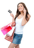 Happy Beautiful woman with shopping bags and credit gift card. Talking on cellular mobile phone, cheerful smiling on a white background Royalty Free Stock Images