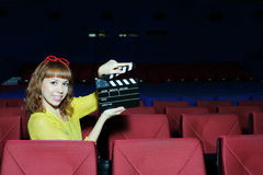Happy beautiful woman shows clap board in auditorium Royalty Free Stock Photography