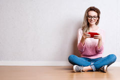 Happy beautiful woman sitting on the floor and using smartphone.  Stock Photo