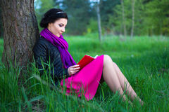 Happy beautiful woman sitting near the tree with book in summer Royalty Free Stock Photo