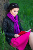 Happy beautiful woman sitting near the tree and reading book in Royalty Free Stock Photos