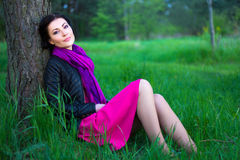 Happy beautiful woman sitting near the tree in summer forest Stock Photo
