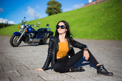 Happy beautiful woman sitting on the road with retro motorbike Royalty Free Stock Photo